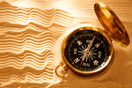 Golden compass with beach sand in closeup