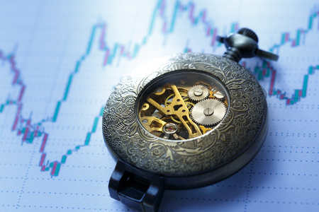 bullish market: Candle stick graph chart of stock market investment trading with a clock Stock Photo