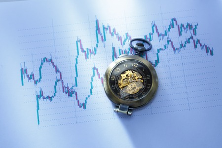Candle stick graph chart of stock market investment trading with a clock Stock Photo