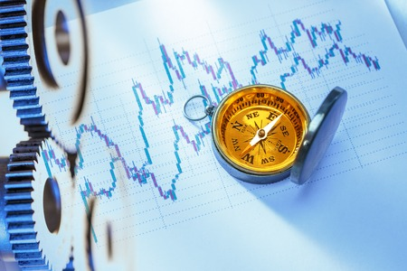 Compass on stock market data chart in closeup Stock Photo