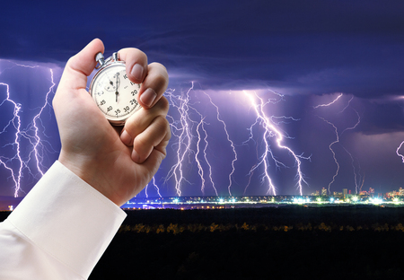 Night thunder lightning over the city sky view and stopwatch in male hand
