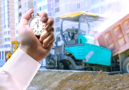 Asphalt-placing machine and stopwatch in male hand Stock Photo