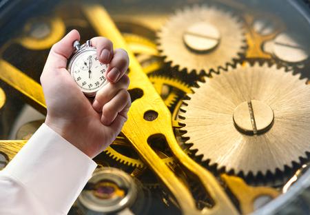 rackwheel: Clockwork inside mechanism and stopwatch in male hand