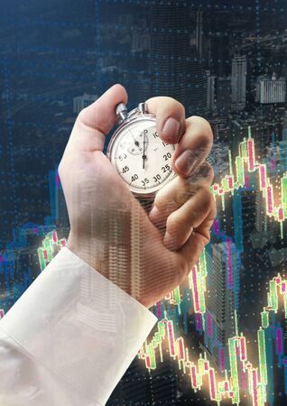 Candlestick chart graphic and stopwatch in male hand