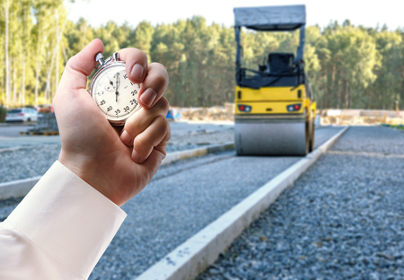 Road roller working and stopwatch in male hand