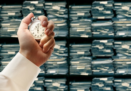 Paper documents stacked archive and stopwatch in male hand