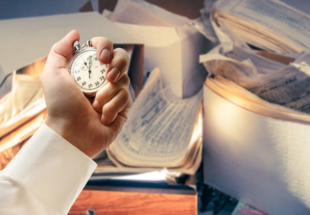 untidy: Messy workplace and stopwatch in male hand Stock Photo