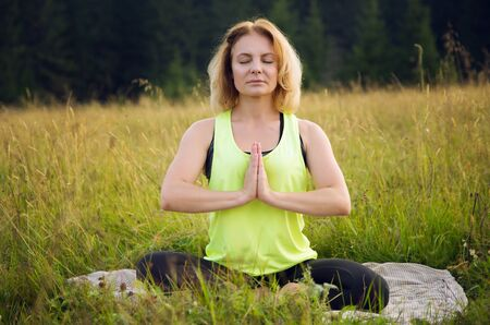 Woman doing yoga outdoors in summer Stok Fotoğraf - 131900906