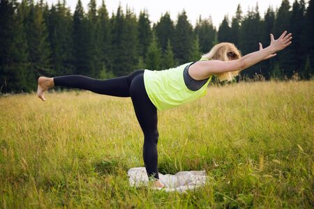 Woman doing yoga outdoors in summer Stok Fotoğraf - 131771675