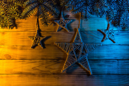 Background of scorched pine boards, with blue spruce branches, homemade stars from twine.