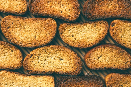 Delicious dried mustard bread. Bread slices on bamboo mats. Bread brown background.