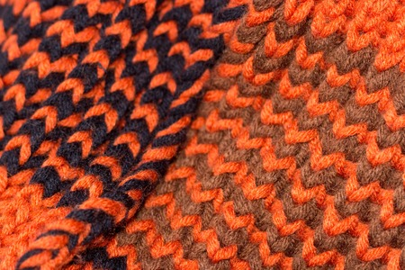 Knitting. Background knitted texture. Bright knitting needles. Orange and black wool yarn for knitting.