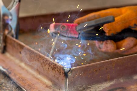 Fastening parts of metal under high temperature using a short circuit. Welding work on the metal. Stock Photo