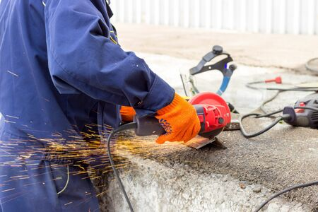 The worker uses an angle drive grinder to work with a metal corner. Angle drive grinder in action.