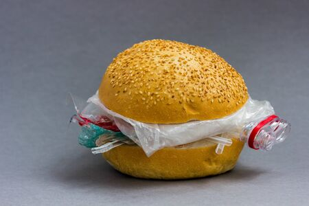 Bun with polyethylene and plastic instead of vegetables and meat. The problem of pollution of the planet with plastic. Ecological problem and trouble.