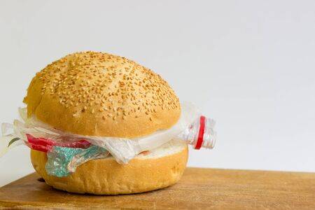 Bun with polyethylene and plastic instead of vegetables and meat. The problem of pollution of the planet with plastic. Ecological problem and trouble. 스톡 콘텐츠