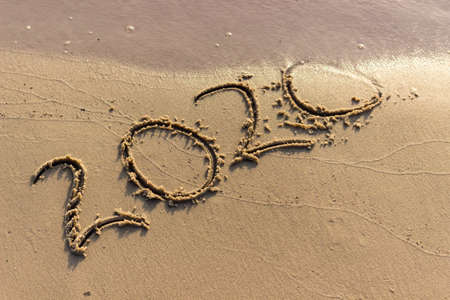 The year 2020 is written on the sandy shore. 2020 comes to an end and is washed away by the wave. Summer background. Banco de Imagens