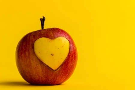 Valentine's Day background. The apple is juicy and fresh with a carved heart in its pulp. Carving for the holiday.