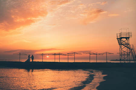 date night: Silhouette of couple on pier at sunset. Date night