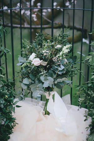 Wedding bouquet of simple white flowers and green leaves in vintage style. The effect of film photography Stock Photo