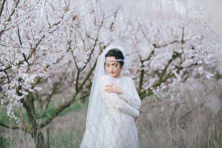 bowing head: Fiancee stands in a spring flowering garden with the closed eyes bowing head to the shoulder hugging itself. The effect of film photography Stock Photo