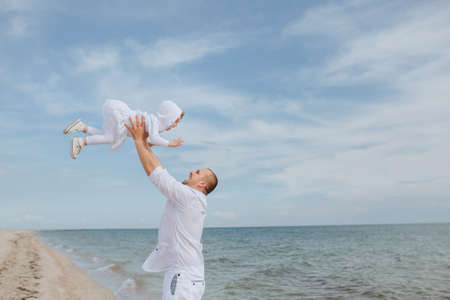 threw: Dad threw up daughter and catches her on the beach. Summer family vacation