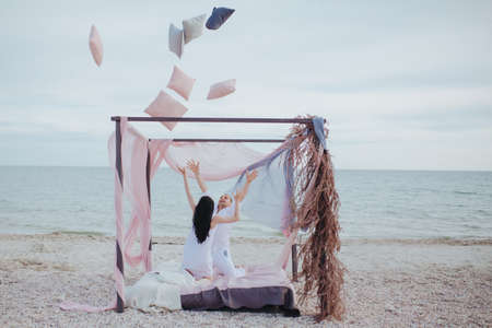 Man and woman tossed up a lot of pillows sitting in the tent on the sea shore. Romantic vacation concept with copy space
