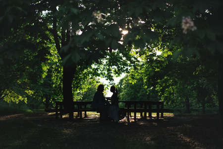 Man and woman sitting in the garden on a bench and look at each other. Beautiful silhouette of couple on background of foliage