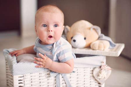 surprised baby: Little surprised baby in white wicker basket
