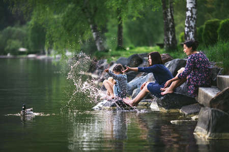 woman squirt: Woman and two girls sit by the lake and play with the duck Stock Photo