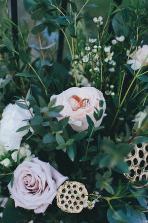Stylish bouquet with pink roses and green plants. Two wedding rings lying in the flower, closeup. The effect of film photography