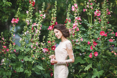 Girl in a wedding dress among the flowers