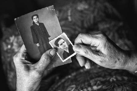 Hände einer alten Frau ein altes Foto zu halten. Konzept der Zeit. Schwarz-Weiß-Fotografie stilisierte