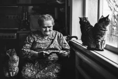 Eine ältere Frau sitzt am Fenster und schaut auf die Karte in ihren Händen