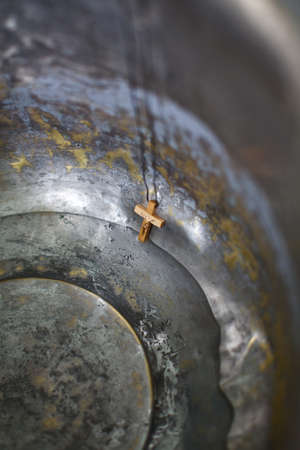 Wooden cross on a thread in an iron tub with water