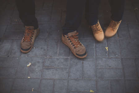 shoestring: Two pairs of legs in brown shoes on the background of gray paving slabs Stock Photo