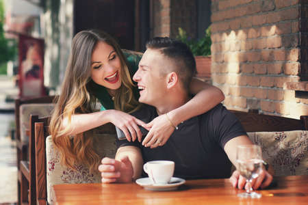 personas abrazadas: Girl embraces the guy behind, both laugh. Guy sits in cafe at a table. On a table a cup about coffee and glass with water