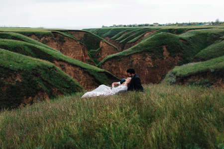 Wedding couple in love sitting on the green grass hill in the mountains smiling touching each other Stock Photo