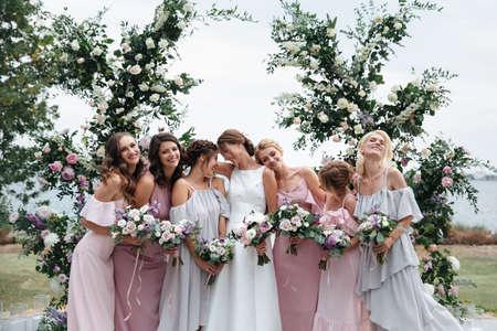 Schöne elegante schlanke lächelnde Brautjungfern im zarten rosa beige Sommerkleid auf der Hochzeitszeremonie Standard-Bild