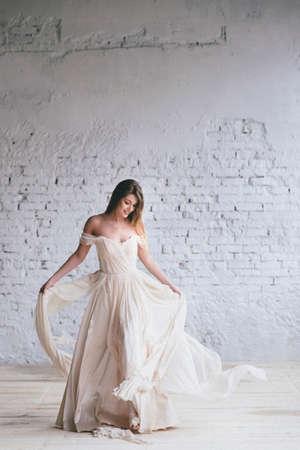 Fashion model in a beautiful beige flowing dress.
