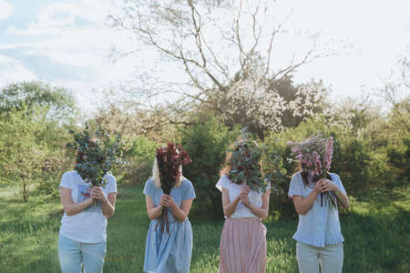 unordinary girls with bouquets in front of their faces. Archivio Fotografico
