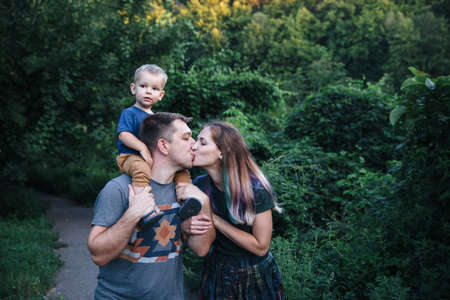 Happy young family father, mother and little son hugging and kissing outdoors, playing together in summer park Stockfoto
