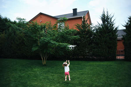The little girl look at the drone in the greengrass garden