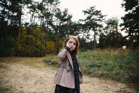 fair-haired girl in a beige coat licking finger on the dry grass and autumn forest background.