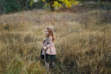 fair-haired girl in a beige coat on the dry grass and autumn trees background.