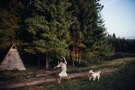 Woman pretty wear amazing white dress and hat are walking with a dog on forest and wooden wigwam background . Perfect place for ceremony. Stock fotó