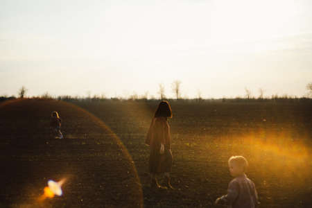 happy family is walking along the wheat field at sunset. The concept of family and love.