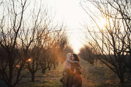happy family is walking along the wheat field near the trees at sunset. The concept of family and love.