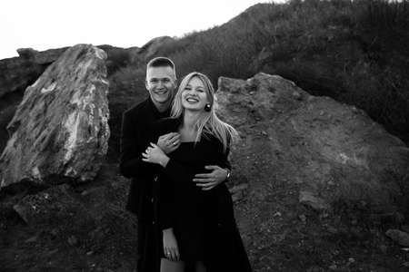 Black and white portrait of two young lovers laught by the sunset on ravine background. Couple in black clothes