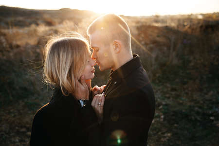 Side view portrait of two young lovers kissing on the sunset